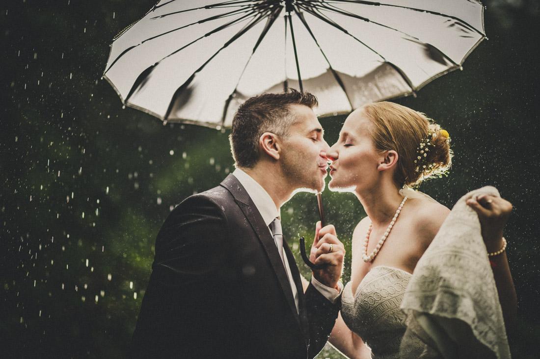 sich im stroemenden regen unter einem schirm kuessendes hochzeitspaar - hochzeitsfotograf dortmund und ruhrpott