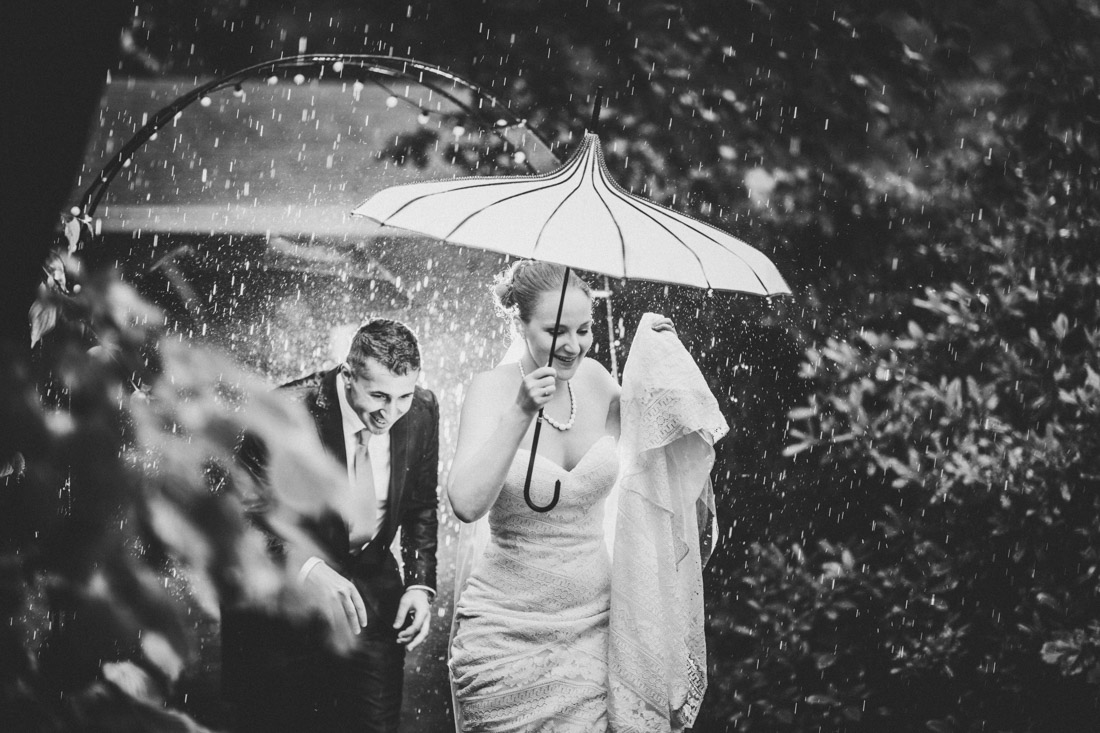 hochzeitspaar im stroemenden regen unter regenschirmen - hochzeitsfotograf dortmund und ruhrpott