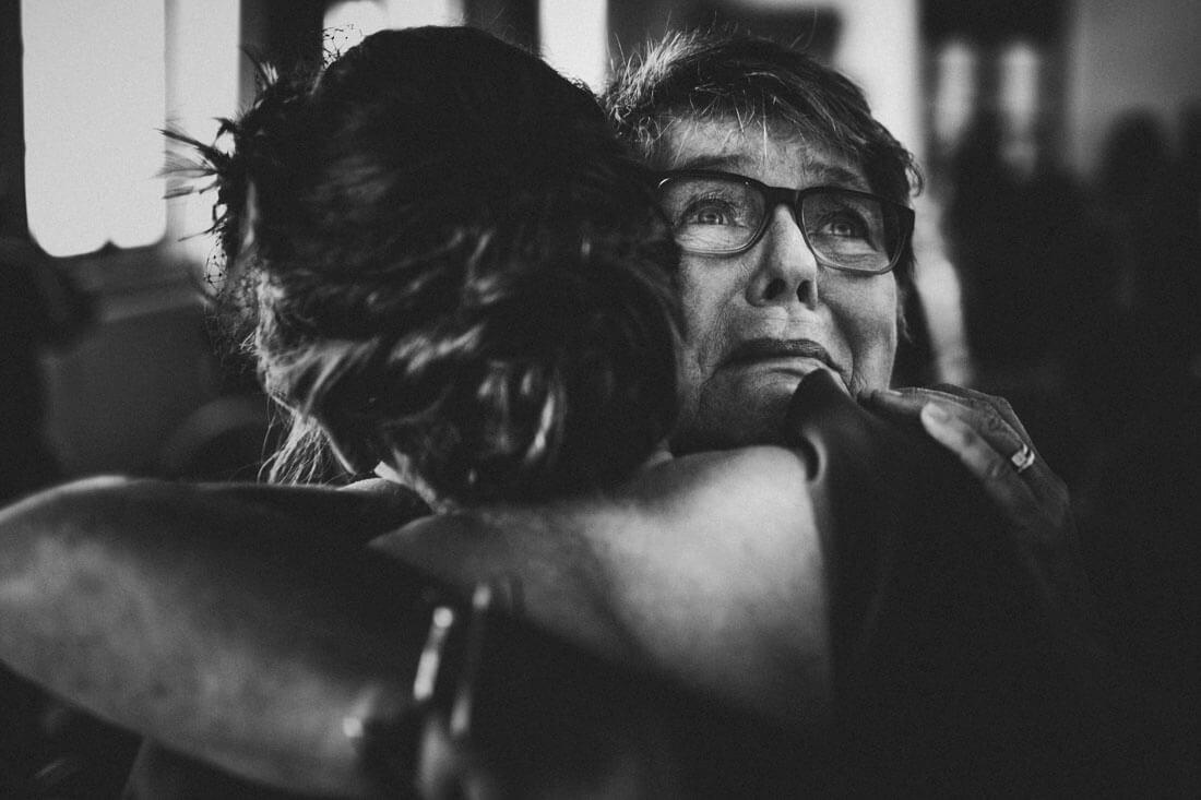 emotional beruehrte mama gratuliert und umarmt ihre tochter nach deren standesamtlicher trauung im fritz-loeffler-saal - hochzeitsfotograf dresden