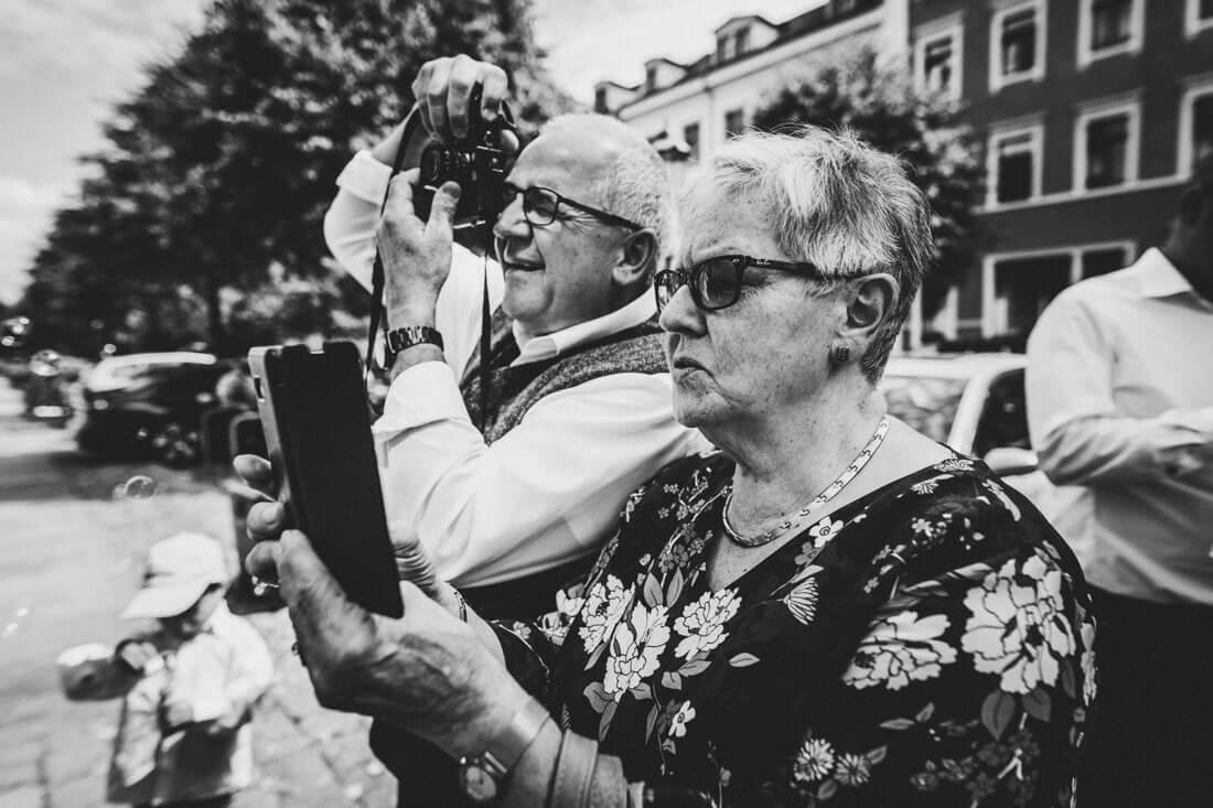 Aufgeregte Gaeste fotografieren enthusiastisch das Brautpaar beim Auszug aus dem Fitz-Loeffler-Saal - Hochzeitsfotograf Dresden