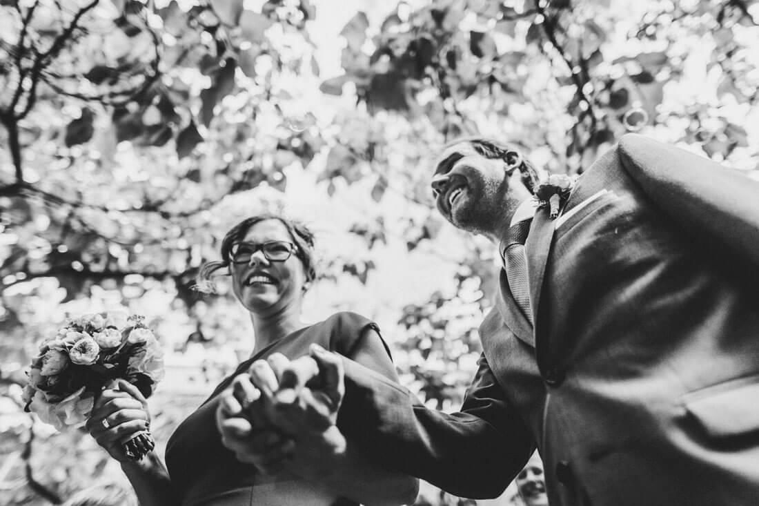 Ueberglueckliches Brautpaar bei der Ankunft zum Sektempfang, aus der Froschperspektive fotografiert - Kuenstlerische und dynamische Hochzeitsfotografie Dresden