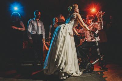 Braut tanzt mit Oma im Rollator