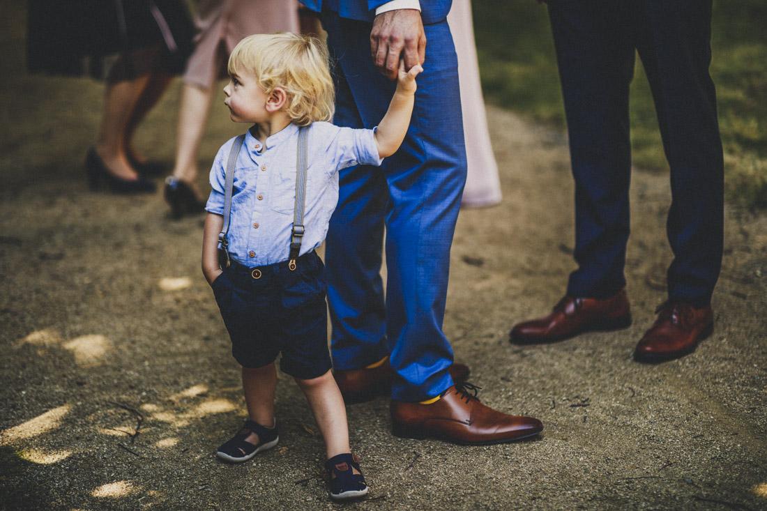 der kleine sohn des hochzeitspaars an der hand seines vaters im schlosspark buseck