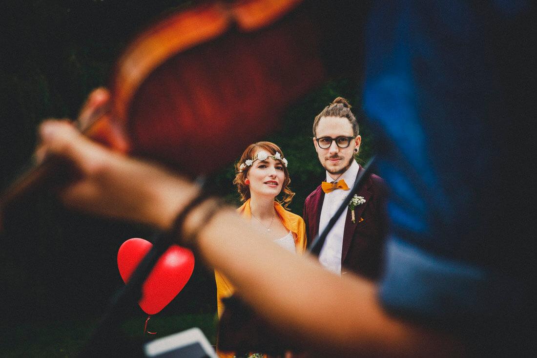 hochzeitspaar blickt zu einem musiker, der ihnen gerade ein staendchen spielt - durch die geige und arm des musikers hindurch fotografiert - hochzeitsfotograf wiesbaden