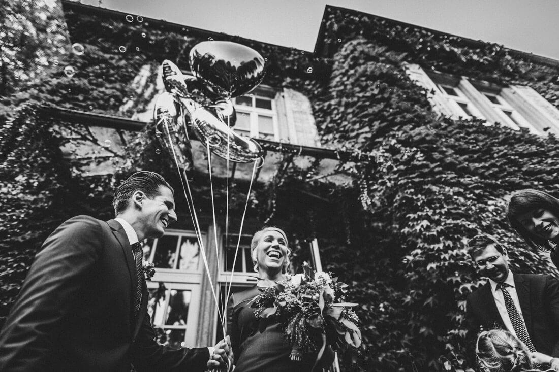 glueckliches freudestrahlendes hochzeitspaar vorm eingang zum zuckerberg-schloss - hochzeitsfotograf schwarzwald