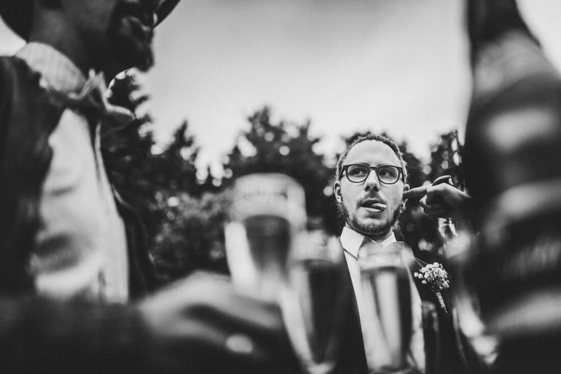 witzige und humorvolle hochzeitsfotos - gast steckt seinen finger ins ohr des braeutigams - hochzeitsfotograf wiesbaden