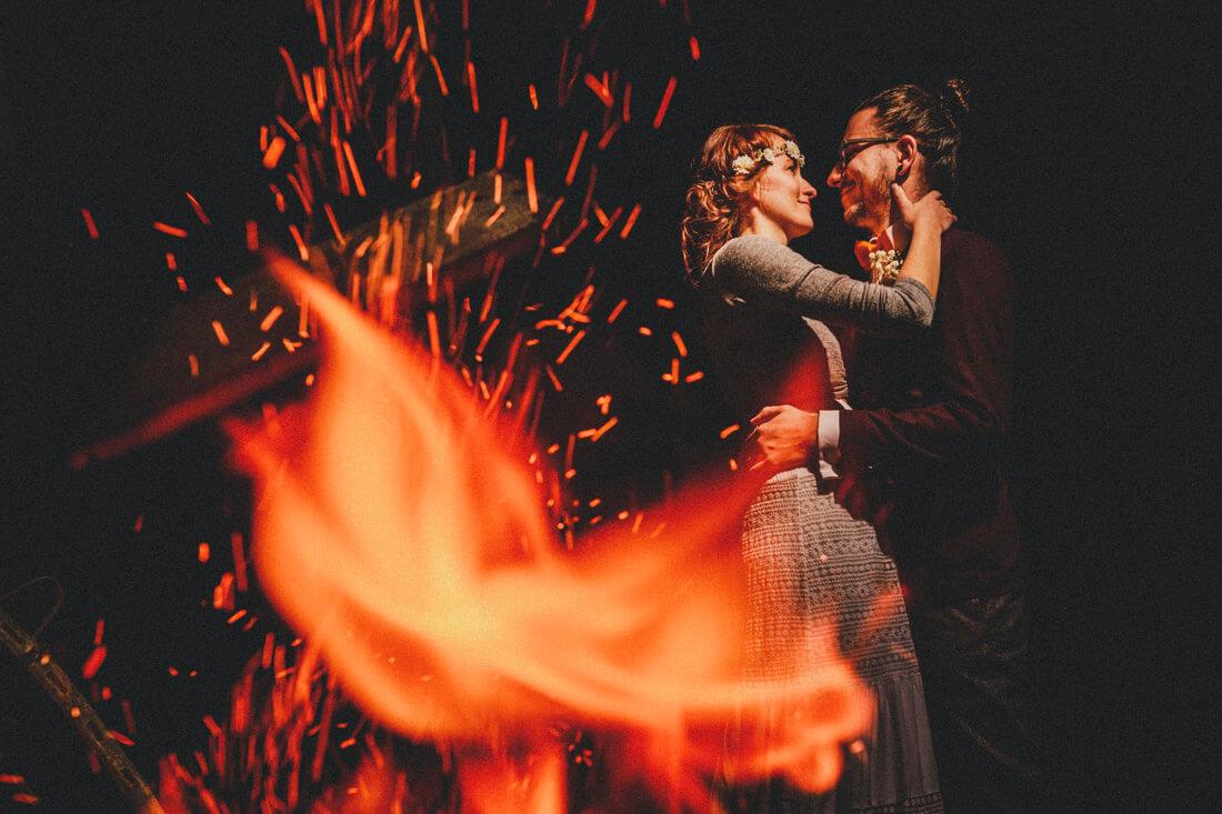 fire-shot, kreatives hochzeitspaar-portraet, durch die funken eines feuers hindurch fotografiert