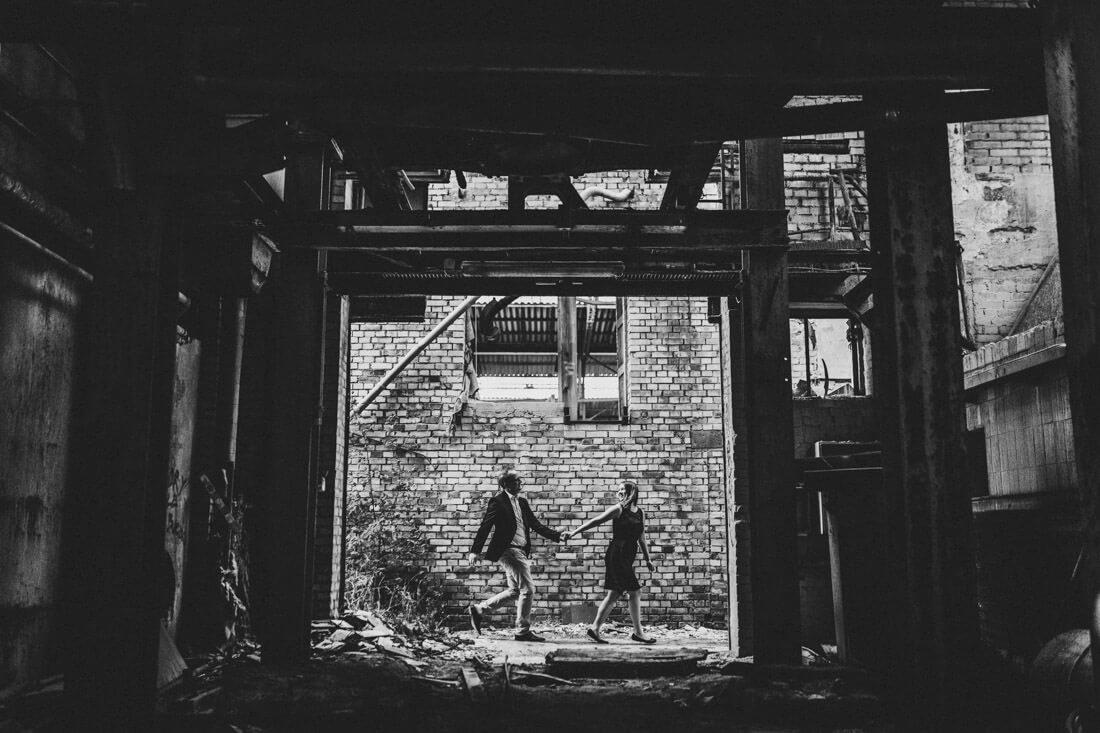 paar laeuft in einer verlassenen location im hintergrund durchs bild, sie schaut sich dabei nach ihm um und nimtm ihn an der hand - love-shooting gießen
