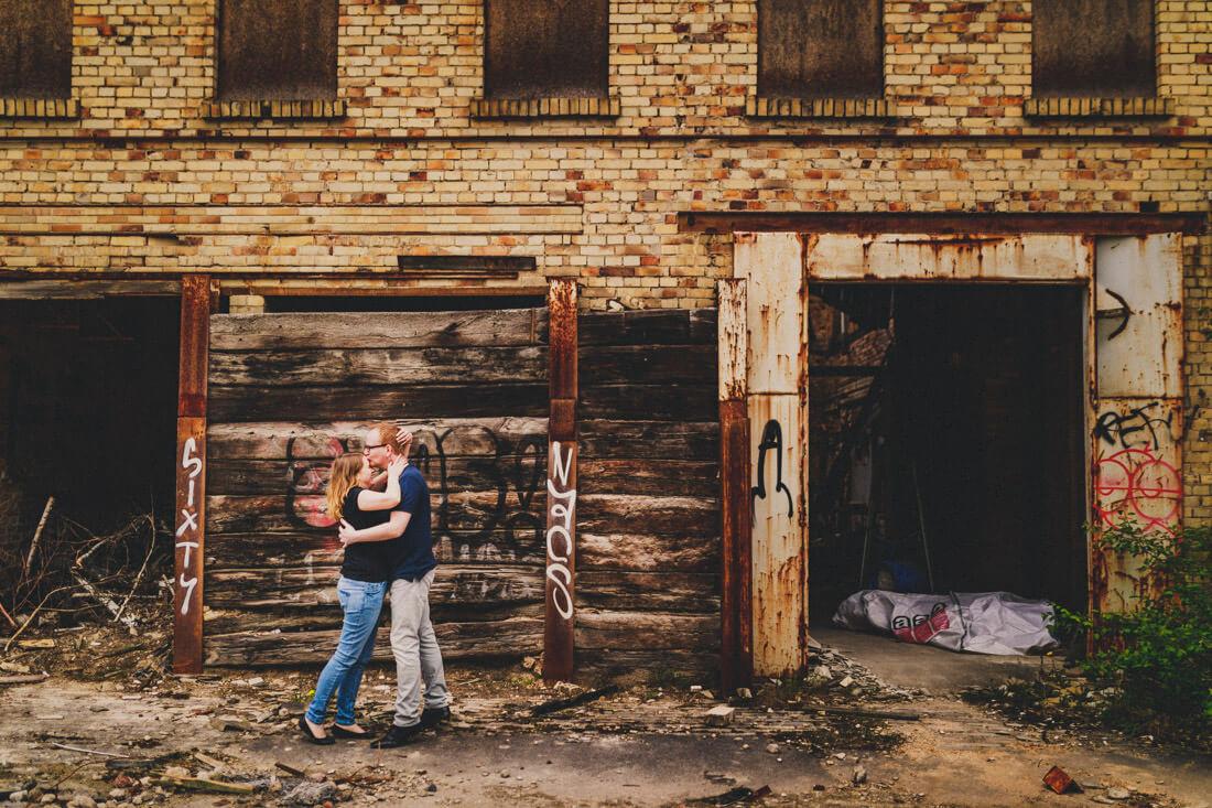 sich innig liebkosendes und umarmendes paar vor der kulisse einer verlassenen fabrik - love-shooting gießen