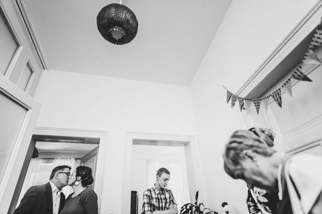 eltern der braut kuessen sich beim get-together im zuhause des brautpaars