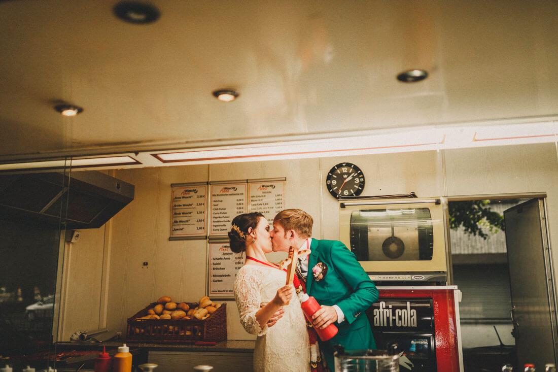 brautpaar kuesst sich hinterm thresen der woscht-anna mit bratwurst in der hand - hochzeitsfotograf giessen