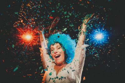 voellig ausgelassen und freudig feiernde braut auf ihrer hochzeit im rotkehlchen in marburg, konfetti in die luft werfend