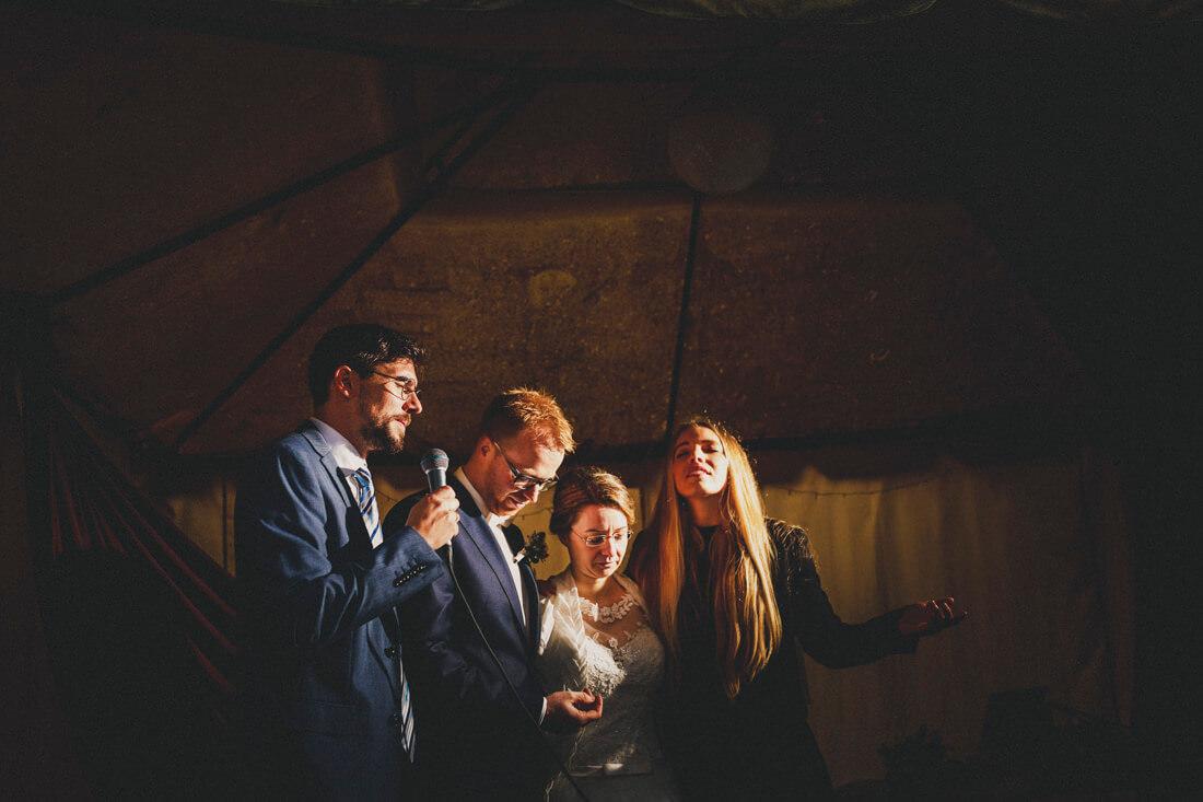 dramatisch illuminierte szene waehrend der trauung, hochzeitspaar und trauzeugen beten in sich versunken - erfahrungsberichte glücklicher hochzeitspaare