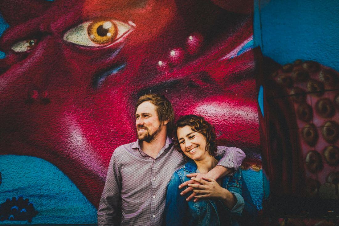 lachendes paar, fotografiert vor einem graffiti eines kraken, dessen blick genau richtung paar gerichtet ist - erfahrungsberichte glücklicher hochzeitspaare