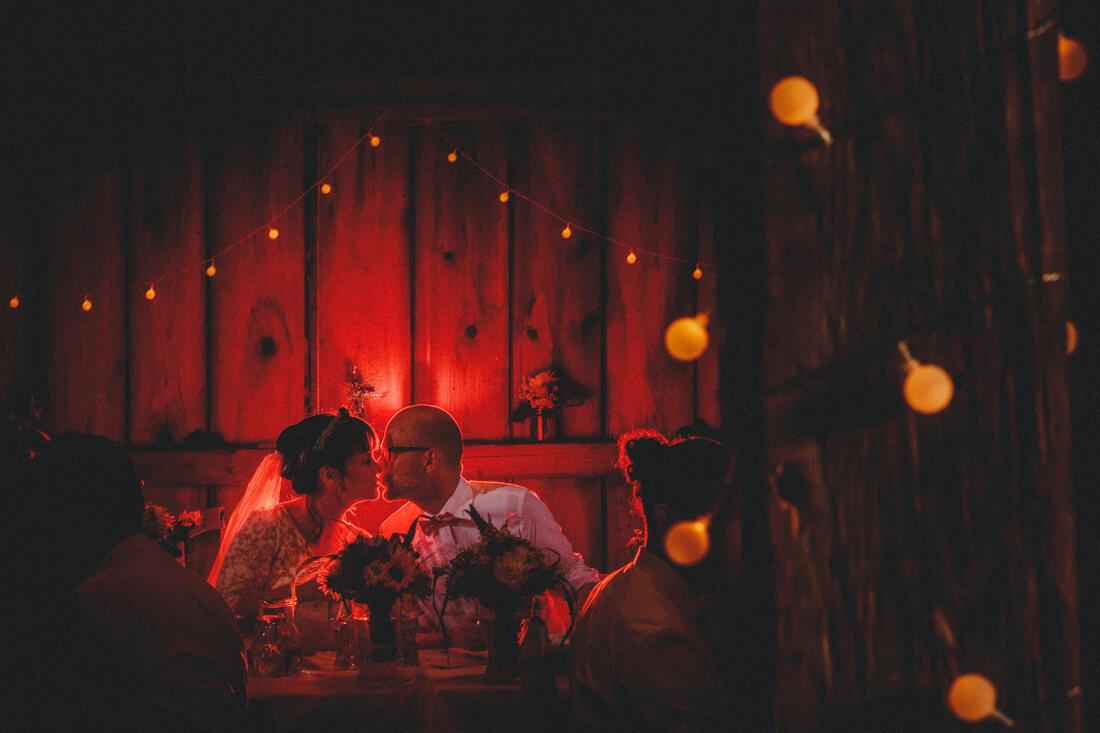 sich kuessendes hochzeitspaar am hochzeitsbankett, mit rotem blitz rueckseitig illuminiert - erfahrungsberichte glücklicher hochzeitspaare